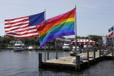 -                In this June 23, 2013 photo, an American flag and a LGBT Rainbow flag are displayed on the ferry dock in the Fire Island community of Cherry Grove, N.Y.  The 1969 Stonewall uprising in