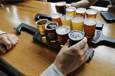 -                In this July 1, 2013 photo, a couple taste a selection of 12 different beer flights at the Beer Hall at the Harpoon Brewery in the Seaport District of Boston.  The neighborhood around t