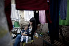 -                In this June 12, 2013 photo, Ailen Nerone, 17, sits with her 4-month-old son Matias at their home, during an interview in Buenos Aires, Argentina. After spending billions on welfare to