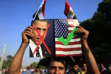 -                An opponent of Egypt's Islamist President Mohammed Morsi holds up a picture showing the United States President Barack Obama and U.S. flag during a rally outside the Presidential palace
