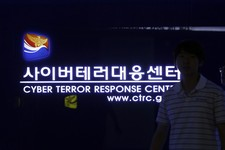 -                In this Friday, July 5, 2013 photo, a man walks by a sign at Cyber Terror Response Center of National Police Agency in Seoul, South Korea. The hackers who knocked out tens of thousands