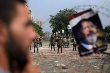 -                A protester stands next to a poster of ousted President Mohammed Morsi hanged on the barb wire as army soldiers guard at the Republican Guard building in Nasr City, Cairo, Egypt, Tuesda