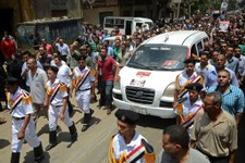 -                Egyptian policemen march with a vehicle carrying the body of their comrade, killed Monday in Cairo outside of the Republican Guard headquarters in an incident that left 51 people dead,