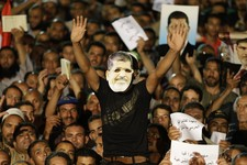 -                A supporter of ousted Egypt's President Mohammed Morsi, wears a mask that shows the face of Morsi during a demonstration after the Iftar prayer, evening meal when Muslims break their fa