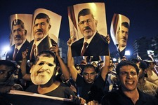 -                In this Wednesday, July 10, 2013 photo, supporters of ousted Egypt's President Mohammed Morsi, hold posters of him as they protest during the Islamic month of Ramadan, in Nasr City, Cai