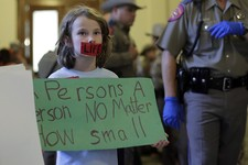 -                Theresa Maska holds a sign supporting anti-abortion legislation outside the Texas Senate as they prepare to debate an abortion bill, Friday, July 12, 2013, in Austin, Texas. The bill wo