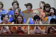 -                Supporters and opponents of an abortion bill, mostly dressed in blue or orange to show their side, sit in the gallery of the Texas Senate chambers as lawmakers debate before the final v