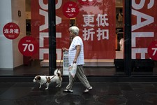 -                A Chinese woman carries a dog walks past a fashion boutique having a sale at a shopping mall in Beijing, China Monday, July 15, 2013. China's leaders face new pressure to stimulate a sl