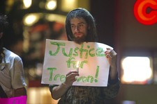 -                Tovia Shapiro of Worcester, Mass. holds a sign and a candle as he stands in the circle in the parking lot of the 7-Eleven in Worcester on the evening of Monday, July 15, 2013 as part of