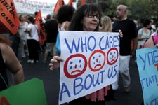 -                A protesting civil servant holds a banner during a rally in central Syntagma Square outside the Greek Parliament in Athens, Monday, July 15, 2013. Some 1,000 people took part in the pea