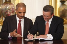 -                Puerto Rico's Governor Alejandro Garcia Padilla, right, signs an agreement as U.S. Attorney General Eric Holder gestures at the governor executive mansion in San Juan, Puerto Rico, Wedn