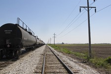 -                This May 14, 2013 photo shows train cars on the tracks that run alongside a field that local economic developers hope to see become a fertilizer plant just outside Tuscola, Ill. A compa