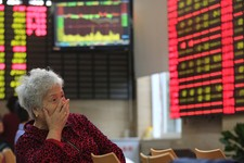 -                FILE - In this Friday, June 7, 2013 file photo, an investor reacts as she looks at the stock price monitor at a private securities company in Shanghai, China. China said Friday it is en
