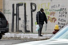 -                FILE - In a Dec. 12, 2008 file photo, a pedestrian walks by graffiti in downtown Detroit. On Thursday, July 18, 2013 Detroit became the largest city in U.S. history to file for bankrupt