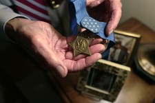 -                In this Friday, July 12, 2013 photo, retired U.S. Navy Capt. Thomas Hudner holds his Medal of Honor, which was awarded by President Truman, at his home in Concord, Mass. Two years after