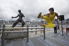 -                Chinese actor Mei Zhiyong dressing as the late Hong Kong Kung Fu star Bruce Lee performs in front of the bronze statue in Hong Kong Saturday, July 20, 2013 to commemorate the 40th anniv