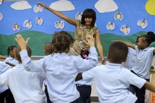 -                FILE - In this May 24, 2013 file photo, first lady Michelle Obama dances with a pre-Kindergarten class at Savoy Elementary School in Washington. The Savoy School was one of eight school