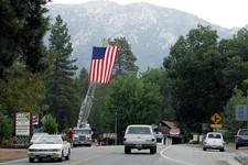 -                A ladder truck flies the American flag to greet residents back to Idyllwild after the evacuation order was rescinded Sunday, July 21, 2013, in the areas affected by the Mountain Fire. T