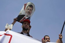 -                A supporter of Egypt's ousted President Mohammed Morsi holds a poster with a photo of him during a demonstration in Cairo, Egypt, Monday, July 22, 2013. The family of ousted Egyptian Pr