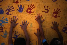 -                Young Syrian refugees touch colorful hand prints on a mural that they made on one of the public bathrooms, at Zaatari refugee camp, near the Syrian border, in Mafraq, Jordan, Tuesday, J