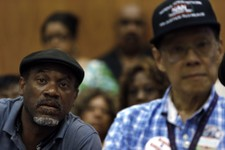 -                Tony Brown, left, a Department of Transportation retiree, listens to union leaders speak in Detroit, Monday, July 22, 2013. Detroit's bankruptcy filing means that thousands of retirees