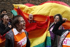 -                Activists shout slogans in support of gay marriage as they wait outside a local court where Carlos Hernando and Gonzalo Ruiz were the first same-sex couple in Colombia to be joined in a