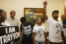 -                At left, American singer, songwriter, actor and social activist Harry Belafonte, Jr. listens as Dream Defenders Executive Director Phillip Agnew, right, raises his fist as he leads a ch