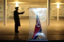 -                In this Monday, July 22, 2013 photo, a North Korean soldier is silhouetted in the background while the North Korean national flag is displayed at the museum of the armistice agreement b