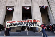 -                FILE - In this July 24, 2013 file photo protesters carry a sign outside the Levin Federal Courthouse in Detroit. Detroit's historic bankruptcy filing is a major setback for public secto