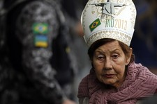 -                A woman wearing a mitre walks past a Brazilian army soldier, as she looks to get in position to get a glimpse of Pope Francis riding past in his popemobile, at the conclusion of the Wor