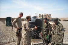 -                This photo taken March 22, 2013 shows U.S. Marine Maj. Chris Bourbeau, left, with the 1st Brigade, 215th Corps Afghanistan National Army Advisor Team, and a translator, at Camp Garmser,