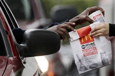 -                FILE - In this Jan. 22, 2010 file photo, a customer grabs lunch at a McDonalds drive-through in Chicago.  Fast-food chains such as McDonald's, Burger King and Wendy's are trumpeting pri