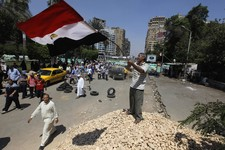 -                A supporter of Egypt's ousted President Mohammed Morsi waves a national flag as he stands on a barrier recently set up where protesters have installed their camp near Cairo University i