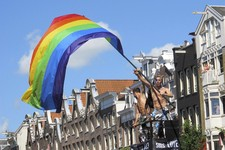 -                A participant waves a rainbow flag during the annual Canal Parade at Prinsengracht in Amsterdam, Saturday Aug. 3, 2013. Rainbow flags are flying from scores of buildings as tens of thou