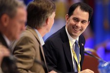 -                Wisconsin Gov. Scott Walker, right, talks to Colorado Gov. John Hickenlooper during a session of the National Governors Association meeting Sunday, August, 4, 2013 in Milwaukee.  Republ