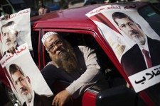 -                A supporter of Egypt's ousted President Mohammed Morsi holds a banner with Morsi's image, during a march against Egyptian Defense Minister Gen. Abdel-Fattah el-Sissi in the Nasr City se