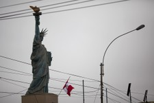 -                In this July 8, 2013 photo, a Peruvian flag flies below a replica of the Statue of Liberty that decorates the entrance of a casino in Lima, Peru. Fines for not flying the Peruvian flag