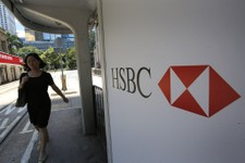 -                A woman walks past a logo of HSBC Holdings at a Hong Kong down town street Tuesday, Aug. 6, 2013. Asian stock markets were mostly lower Tuesday despite an upbeat report on U.S. service