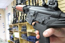 "-                In this Feb. 1, 2013 photo, an employee of North Raleigh Guns demonstrates how a ""bump"" stock works at the Raleigh, N.C., shop. The accessory devices, which legally allow a semiautomati"
