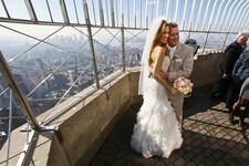 -                Newlyweds Danielle Brabham, 39, and Michael Lynch, 41, from Miami Shores, Fla., pose for pictures at the Empire State Building viewing platform after their Valentine's Day wedding on Th