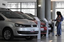 -                In this Feb. 1, 2013 photo, a couple looks at the price of a new vehicle that has already been sold, parked next to other already sold cars on display at a Volkswagen salesroom in Carac