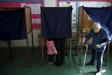 -                A woman, right, leaves a polling booth as a mother with her child votes in an other booth in the Presidential election in southern port city of Limassol, Cyprus, Sunday, Feb. 17, 2013.