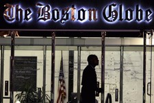 -                FILE - In this July 20, 2009 file photo, a security guard walks past the entrance of The Boston Globe building in the Dorchester neighborhood of Boston. The New York Times Company, whic