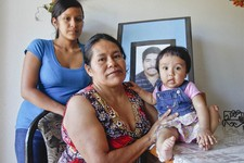 -                In this June 25, 2012 photo, Juana Garcia Martinez, with her daughter, Gladys Dominguez, 19, left, and granddaughter, Jazleen Dominguez, 8-months-old, pose in front of a photo of Juana