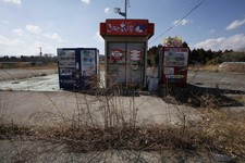-                In this Tuesday, March 5, 2013 photo, weeds grow near drinks and rice vending machines in the abandoned town of Naraha, which was once inside the nuclear exclusion zone surrounding the
