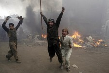 -                Pakistani men, part of an angry mob, react after burning belongings of Christian families, in Lahore, Pakistan, Saturday, March 9, 2013. A mob of hundreds of people in the eastern Pakis