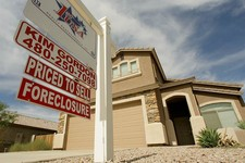 -                FILE - In this Sept. 26, 2007 file photo, a realty sign stands in front of one of the many homes that are in foreclosure in the Villages of Queen Creek in Queen Creek, Ariz. The number