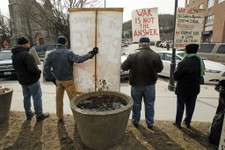-                In this March 15, 2013 photo, protesters hold signs in front of the federal building in Montpelier, Vt. More than a decade after anti-war protesters started a weekly vigil in front of t