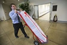 -                A Senate aide delivers a stack of documents bound in red tape being used as a prop during debate on the budget in the Senate, at the Capitol in Washington, Friday, March 22, 2013. The p