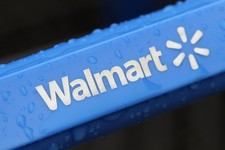 -                FILE - This Nov. 14, 2011 file photo shows the rain-soaked handle of a shopping cart outside the Walmart store in Mayfield Heights, Ohio. Wal-Mart Stores Inc. will be testing this summe